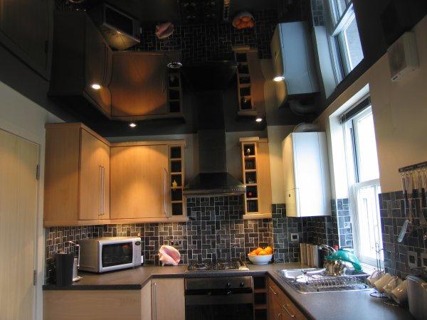 Черный глянец на кухне-экзотичное решение в сочетании со светлыми фасадами