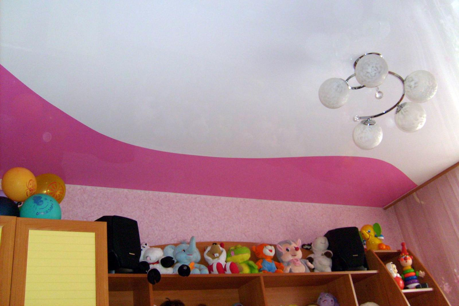Криволинейный потолок из глянцевого цветного и белого полотна и установкой потолочной люстры