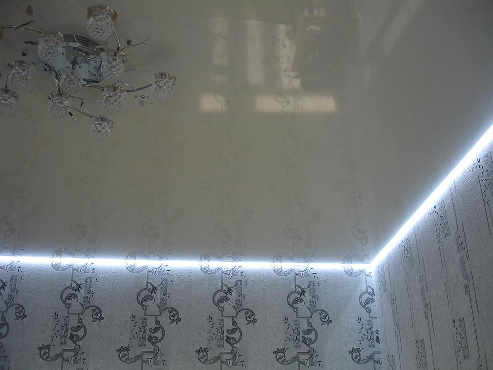 Белый глянцевый потолок в гостиную с парящим профелем и белой светодиодной лентой
