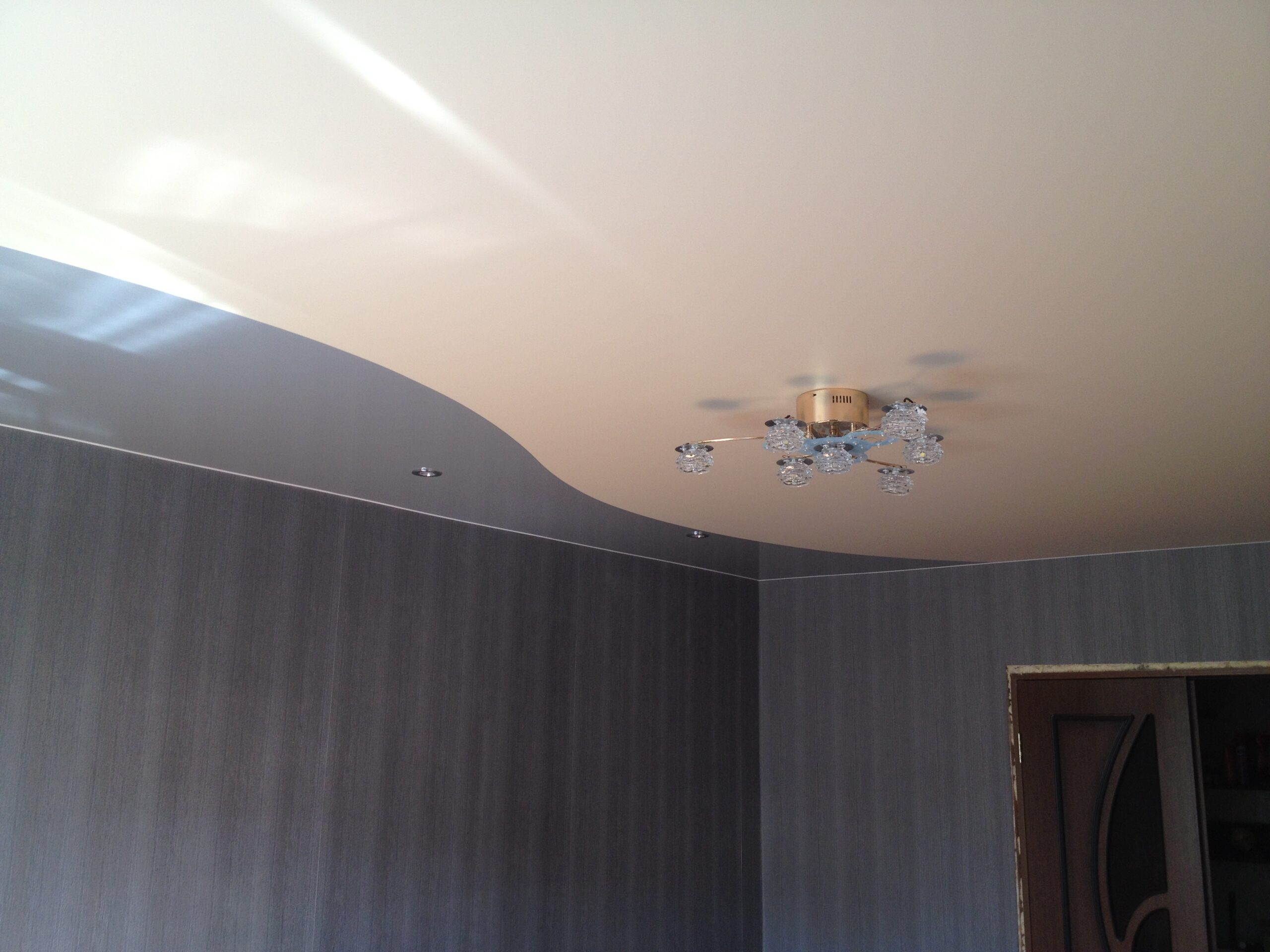 Криволинейный потолок разных фактур и цветов с установкой потолочной люстры и точечных светильников