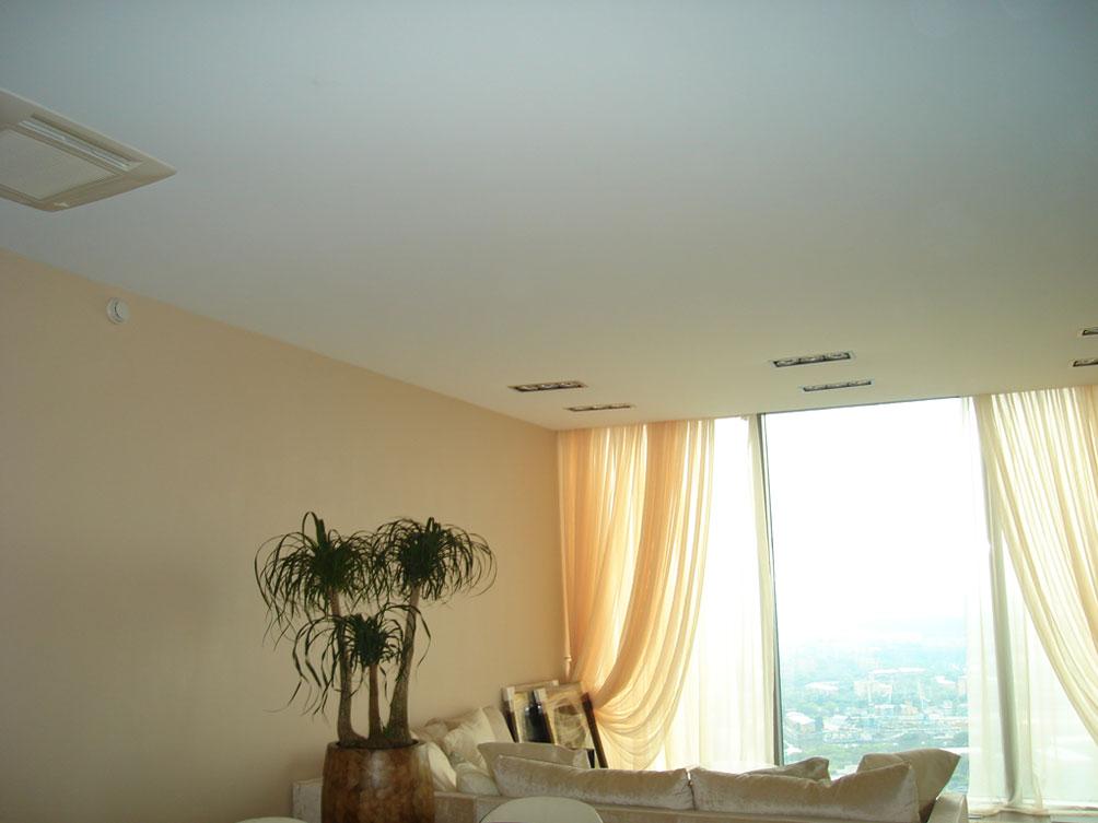 Матовый бесшовный, белый потолок с встроенными светильниками и скрытым карнизом