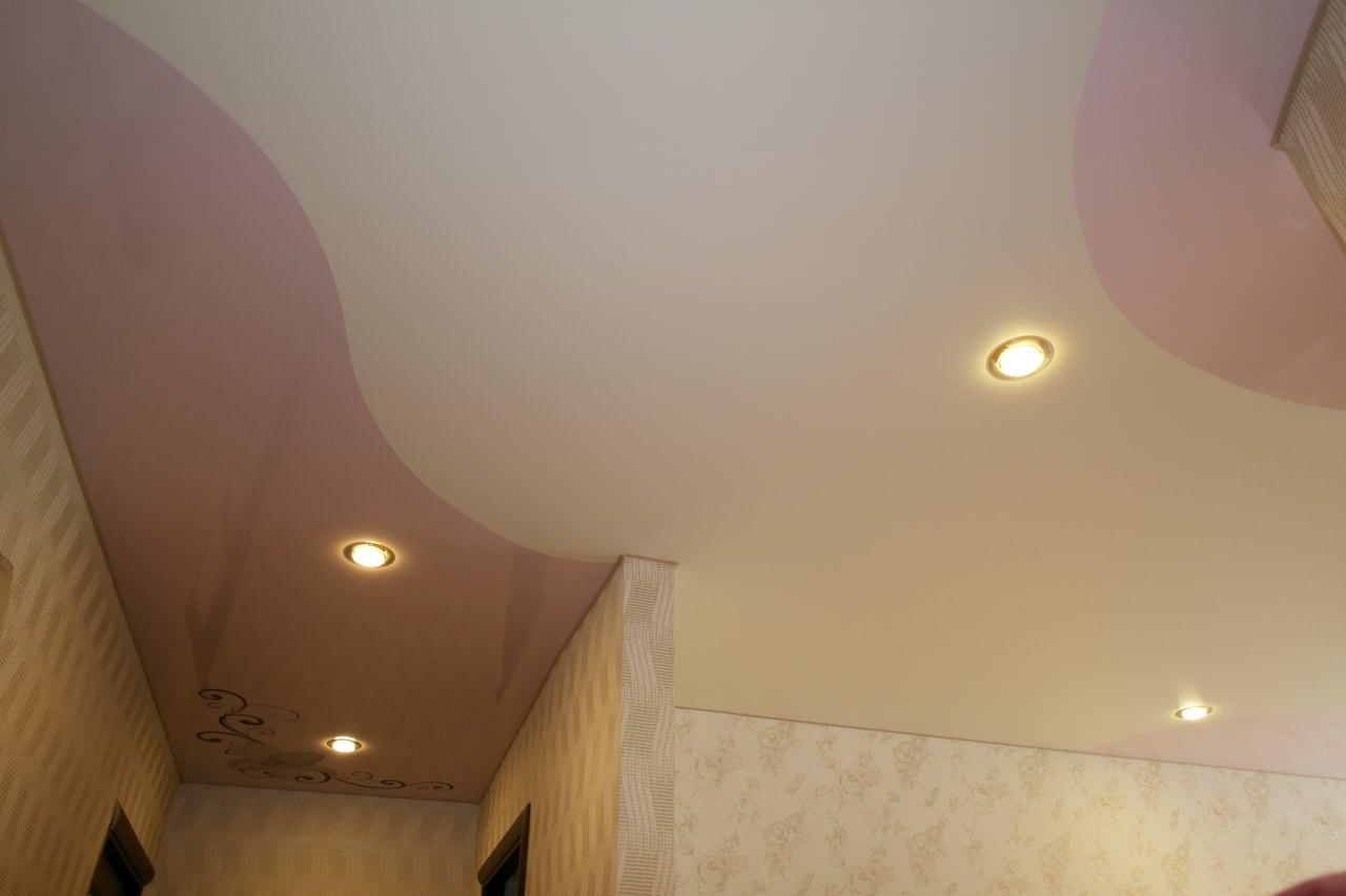 Криволинейный потолок в сочетании матовой и глянцевой фактуры с фрагментом арт печати и установкой точечных светильников- отлично подчеркнет индивидуальности вашего помещения
