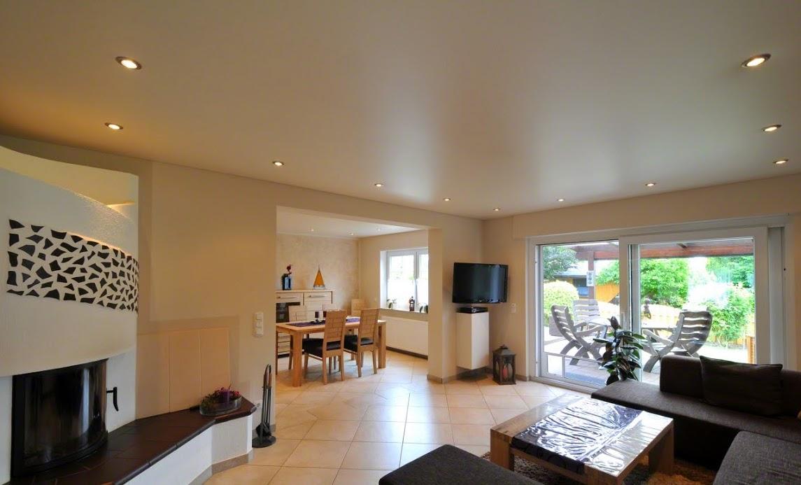 Сатиновый белый потолок с встроенными светильниками по периметру в гостиной с камином