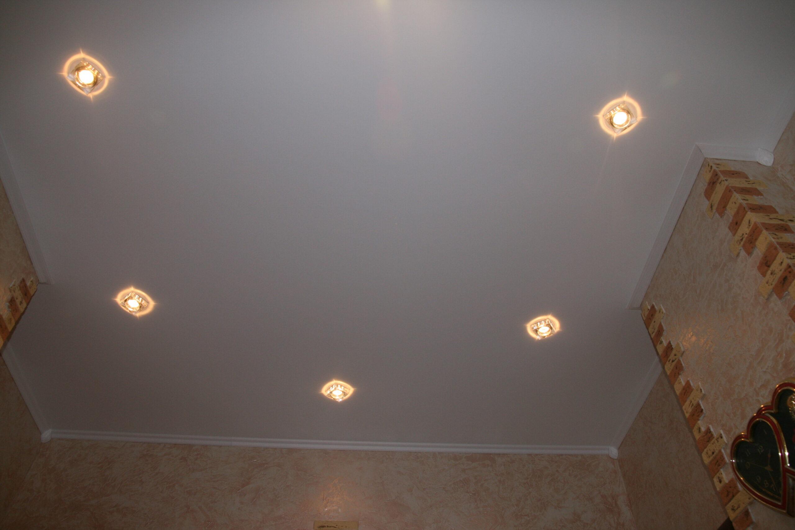Матовый бесшовный, белый потолок в спальне с камином