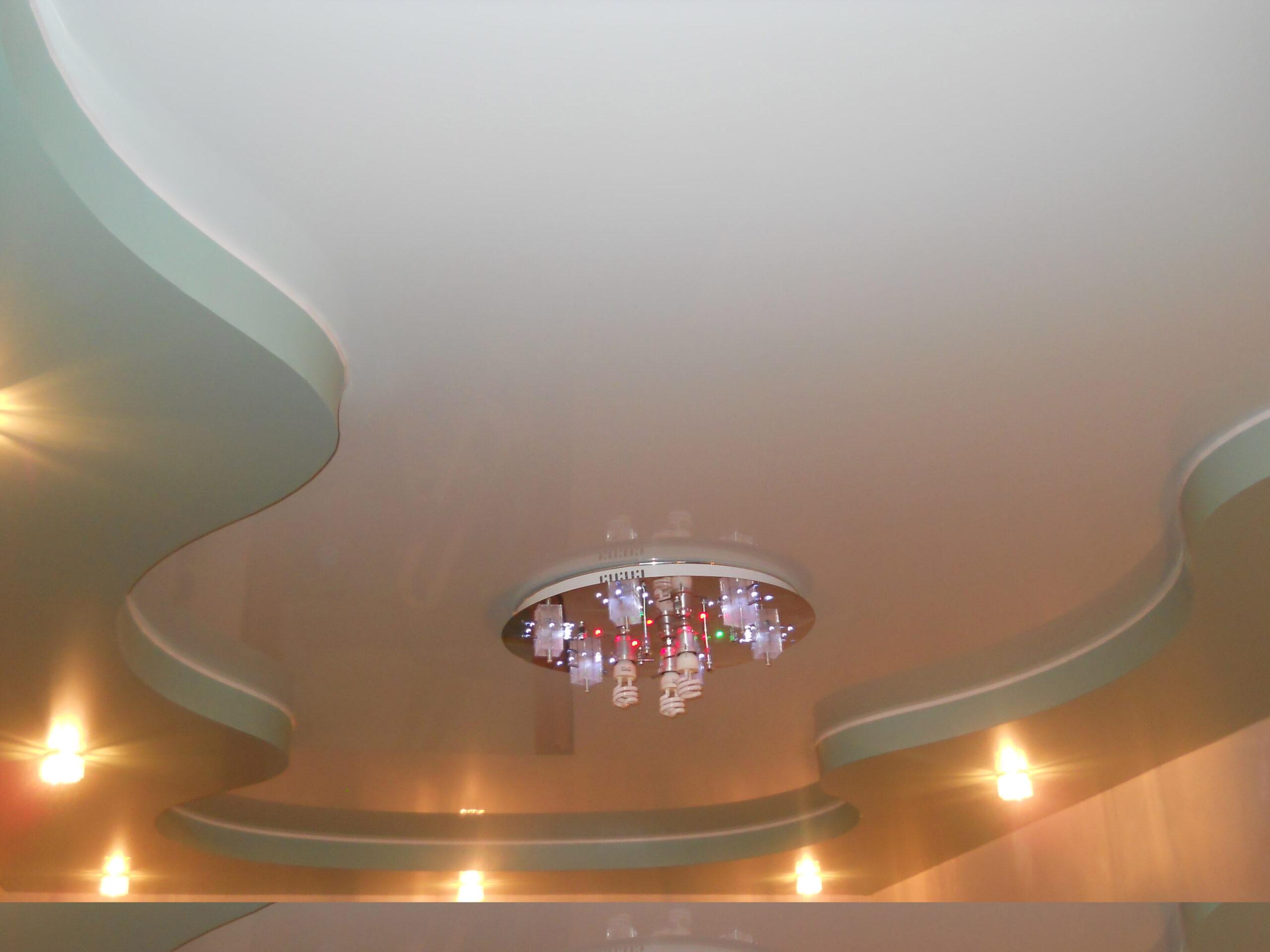 Двухуровневый тканевый потолок с установкой люстры и точечных светильников
