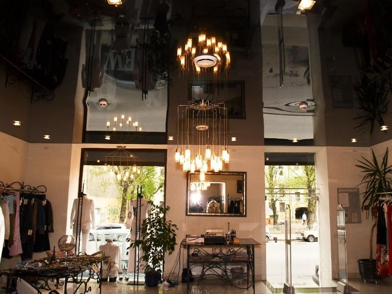 Глянцевый темно-коричневый потолок с встроенными светильниками и дизайнерской люстрой для торговых залов
