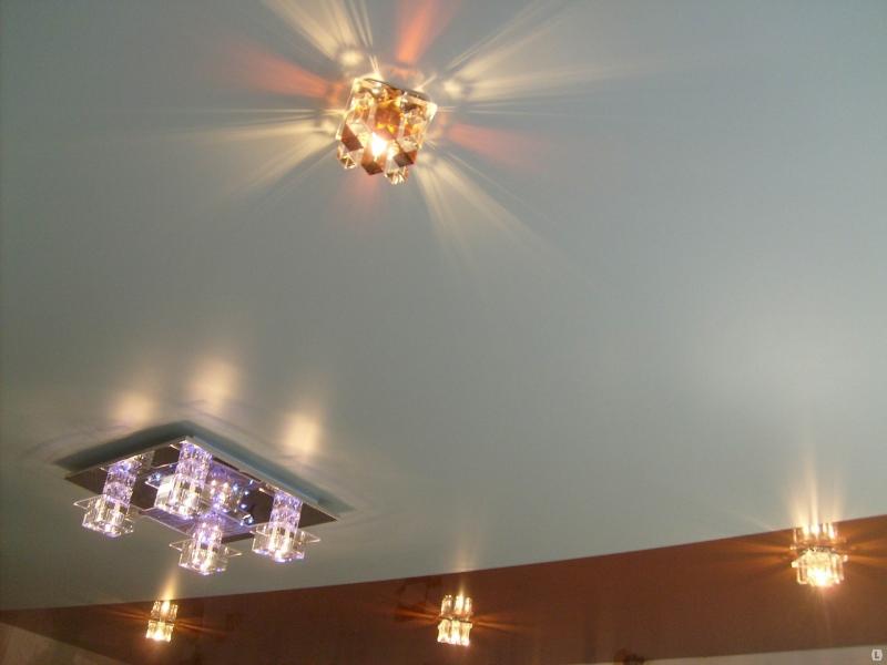 Матовый белый потолок с люстрой и кадратными светильниками