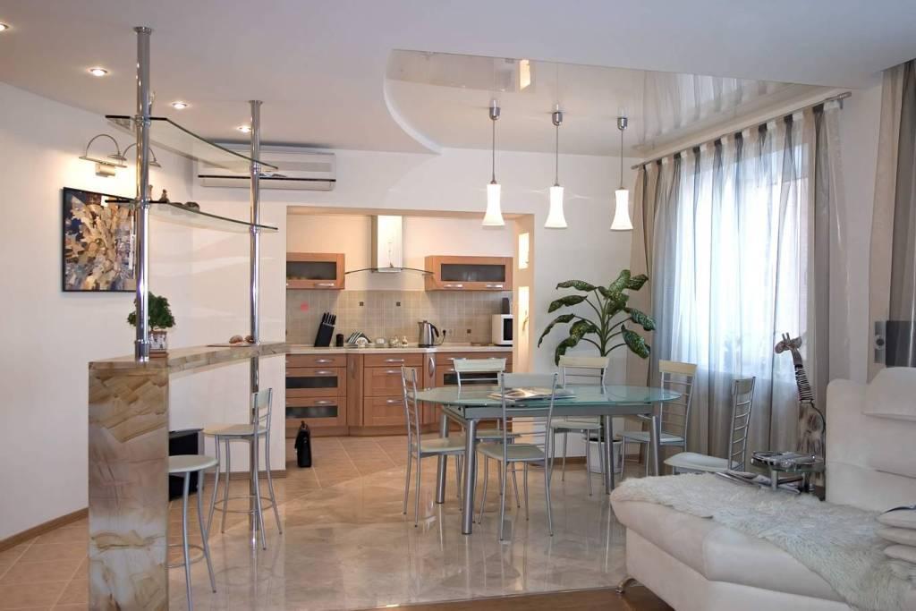 Двухуровневый белый потолок с разными фактурами полотен, установкой люстры и точечных светильников