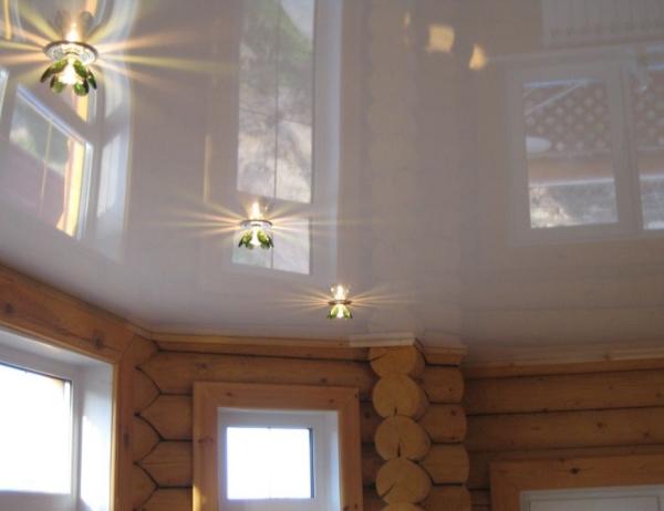 Глянцевый белый потолок с установкой светильников в деревянном загородном доме на даче
