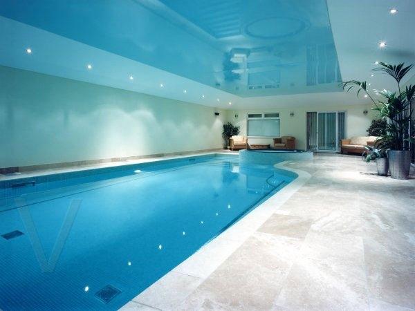 Голубой глянцевый натяжной потолок в бассейне со светильниками по периметру