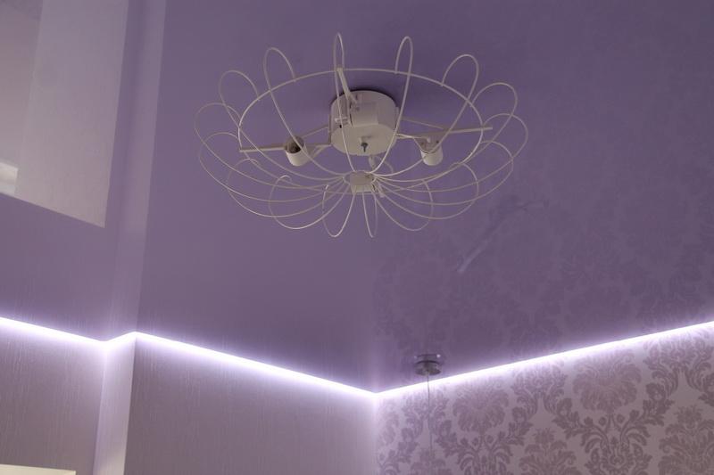Белый глянцевый парящий потолок с люстрой в спальне