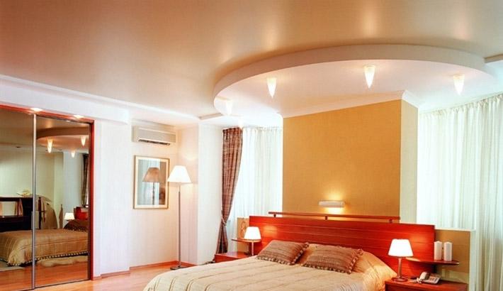 Сатиновый белый потолок с двухуровневой криволинейной конструкцией над спальным местом