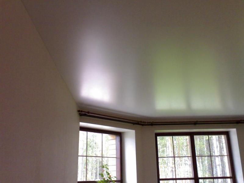 Сатиновый белый потолок у эркерных окон в загородном доме