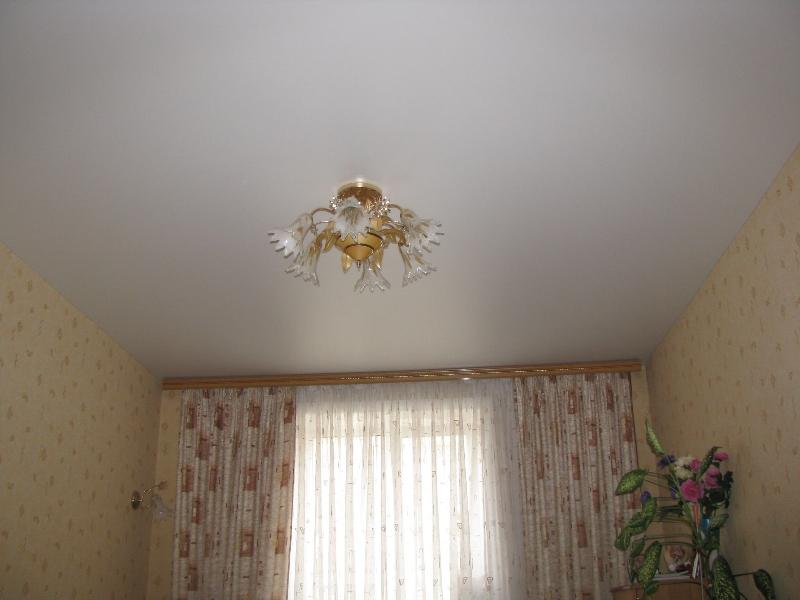Сатиновый белый бесшовный потолок с потолочной люстрой в гостиной