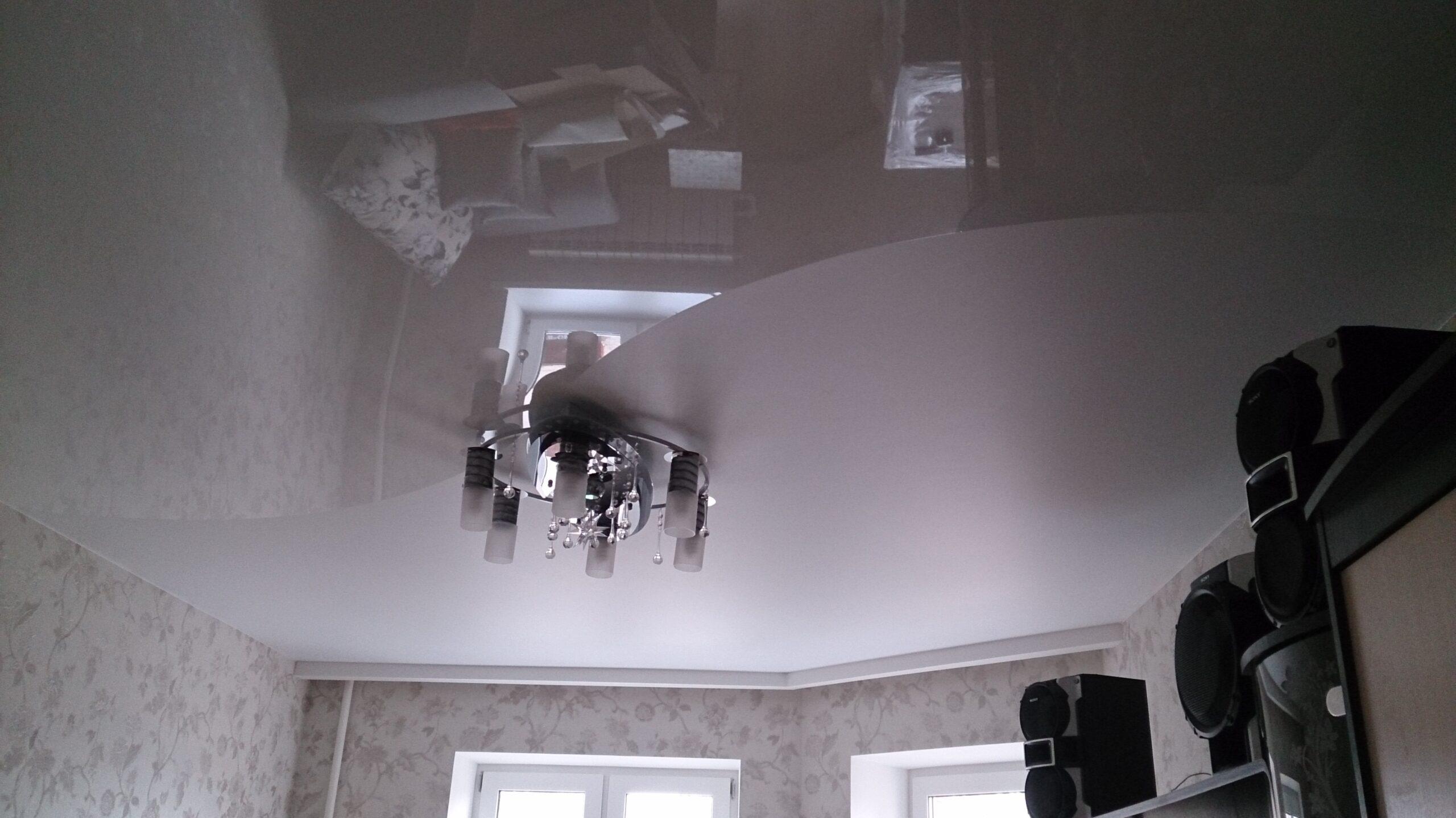 Белый криволинейный потолок с разными фактурами и установкой потолочной люстры