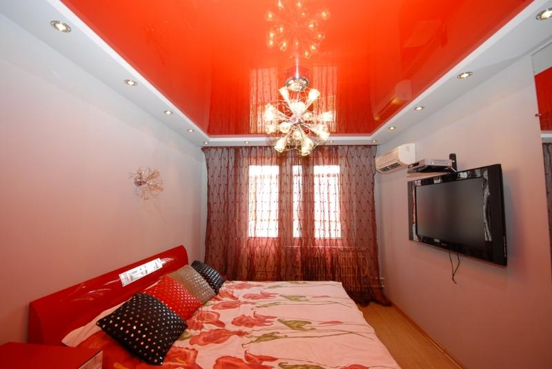 Двухуровневый потолок с разными цветами и фактурами с установкой точечных светильников и люстры-это яркое и креативное решение для вашей спальни