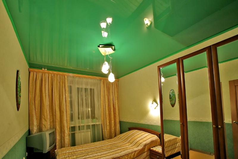 Яркий глянцевый потолок с установкой люстры- необычное решение для творческих людей