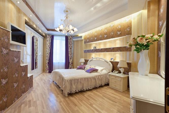 Двухуровневый глянцевый потолок с установкой люстры, точечных светильников и светодиодной ленты теплого света, придадут атмосферу уюта и тепла вашей спальне
