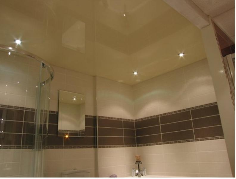 Глянцевый бежевый потолок с установкой точечных светильников подчеркнет элегантность и индивидуальность ванной комнаты