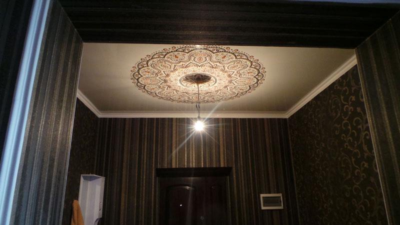 Эффектный рисунок на натяжном потолке вокруг люстры в пригоже прекрасно подчеркнет ее симметрию
