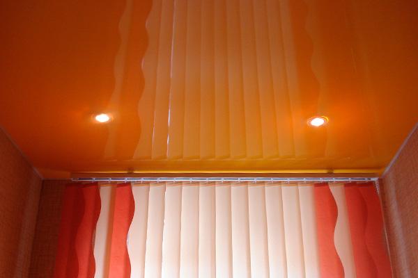 Оранжевый глянцевый потолок со светильниками на кухне