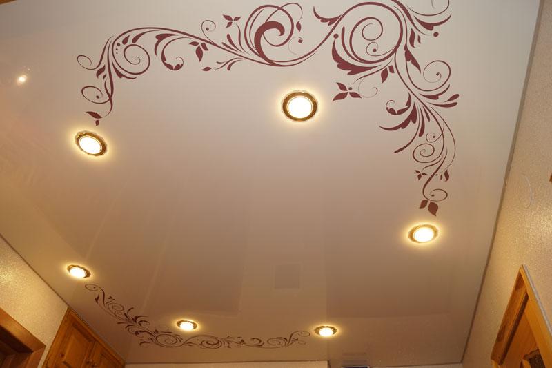 Рисунок на натяжном потолке в виде изящных линий вокруг светильников Ecola