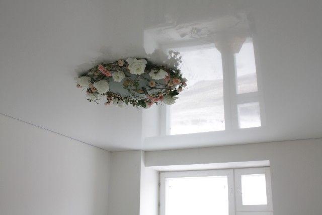 Красивый белый глянцевый натяжной потолок в интерьере гостиной