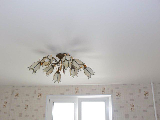 Белый матовый потолок с люстрой в спальне