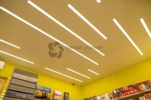 белый матовый потолок со световыми линиями в магазине